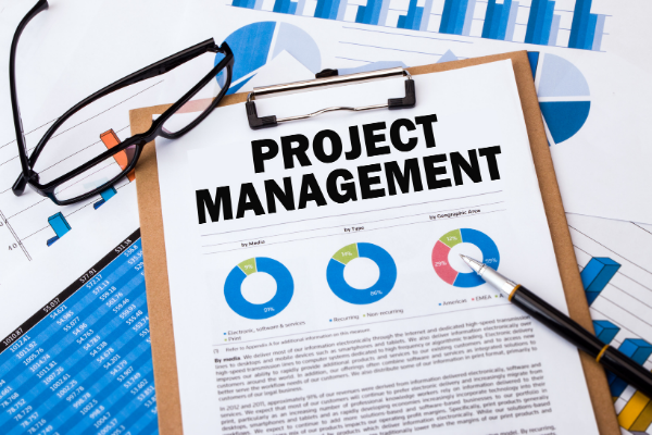 """Photo illustration of clipboard with paper saying, """"Project management."""""""